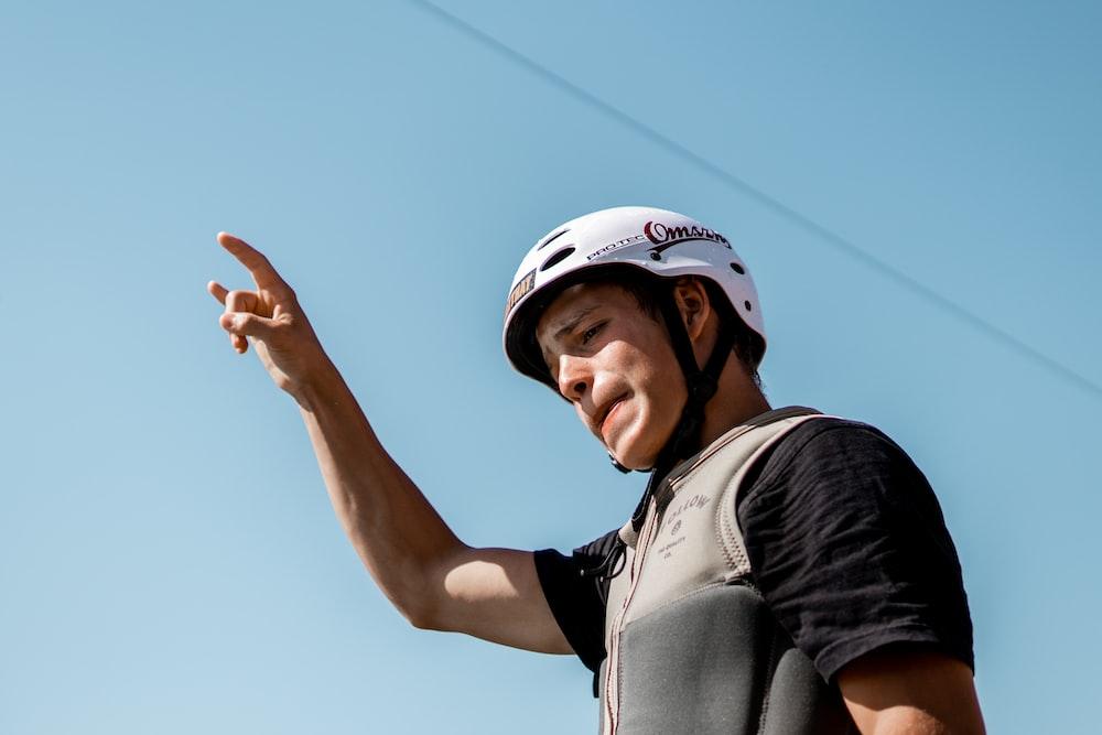 man in black and white shirt wearing white cap raising his right hand