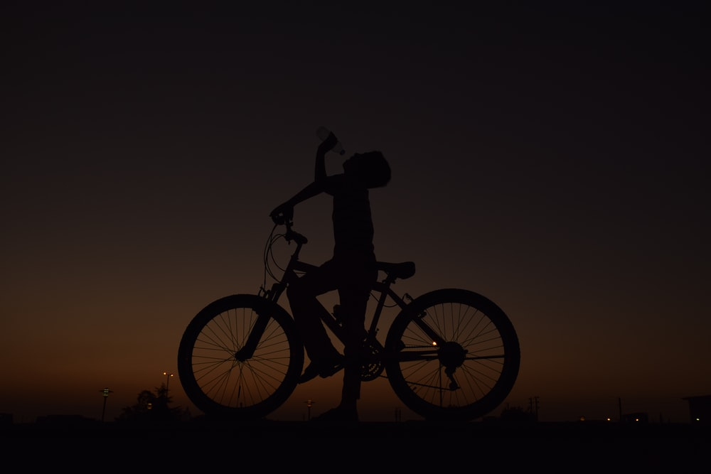 silhouette of man riding bicycle during sunset