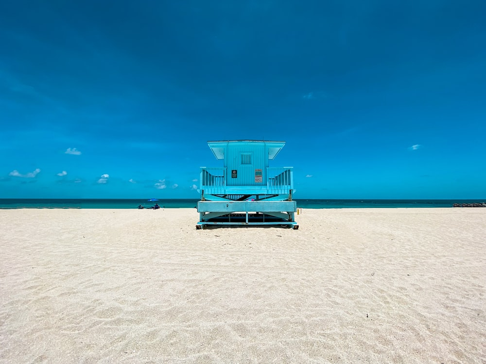blue and white lifeguard house on beach during daytime