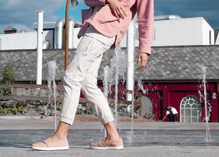 woman in pink jacket and white pants standing on gray concrete floor during daytime