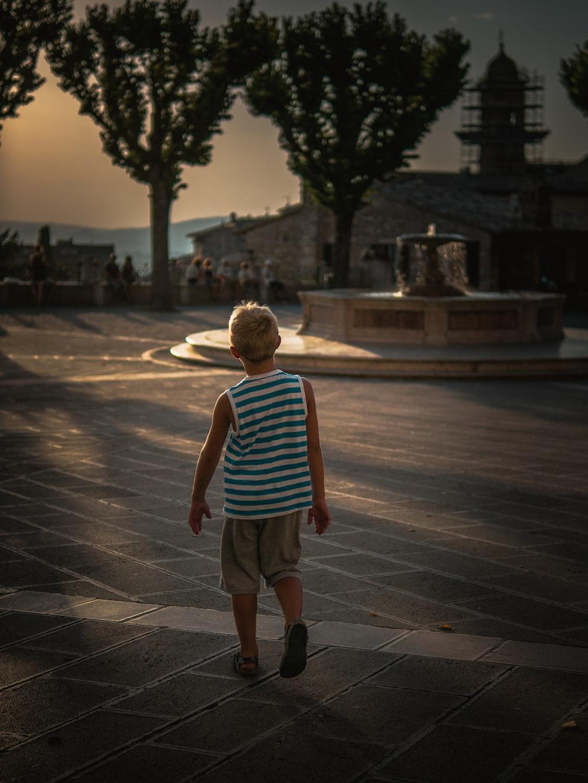 boy in blue and white stripe tank top walking on sidewalk during daytime