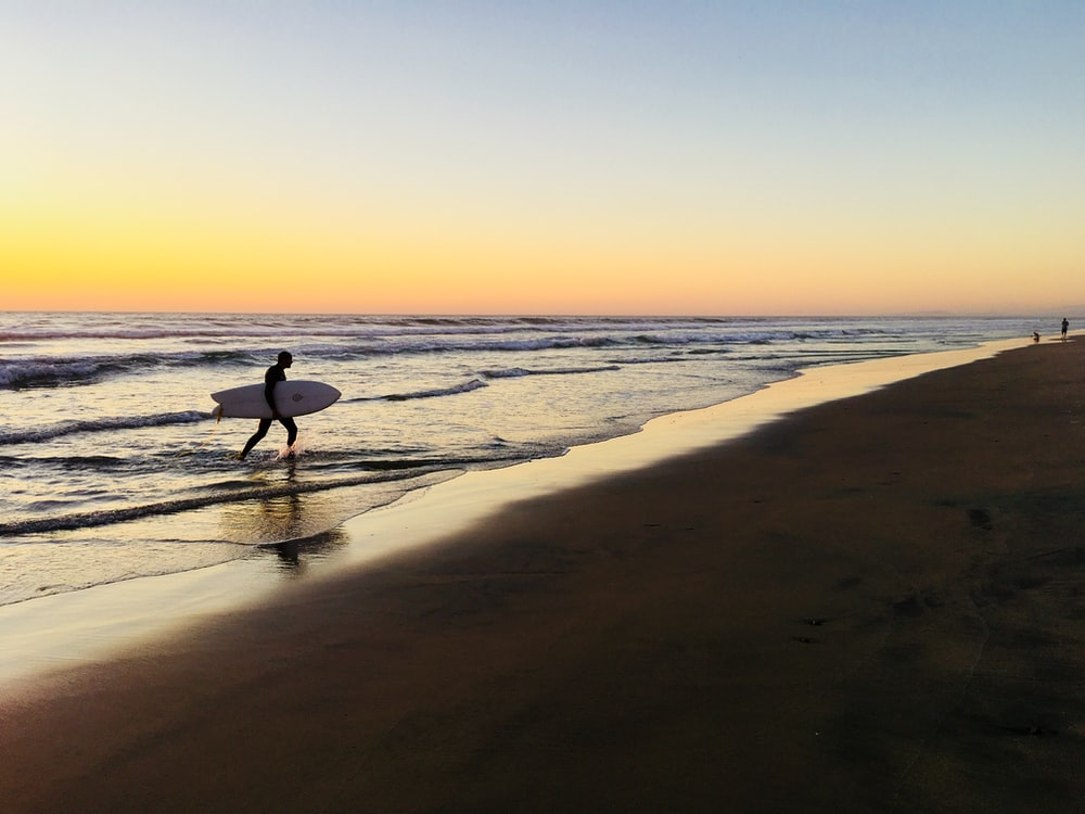 silhouette of man walking on beach during sunset