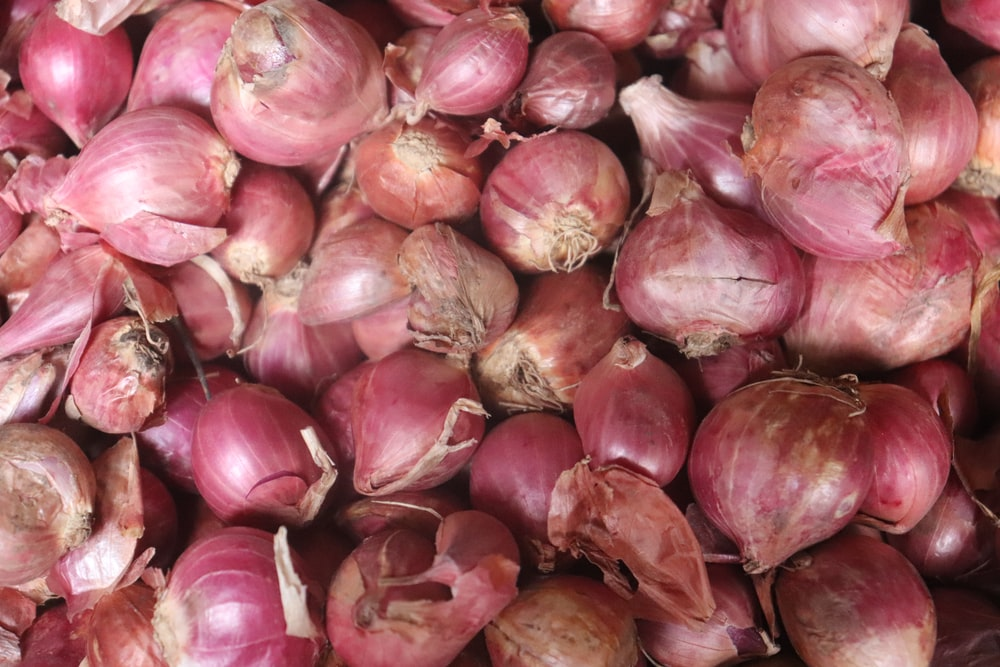 red onion bulbs on brown wooden table
