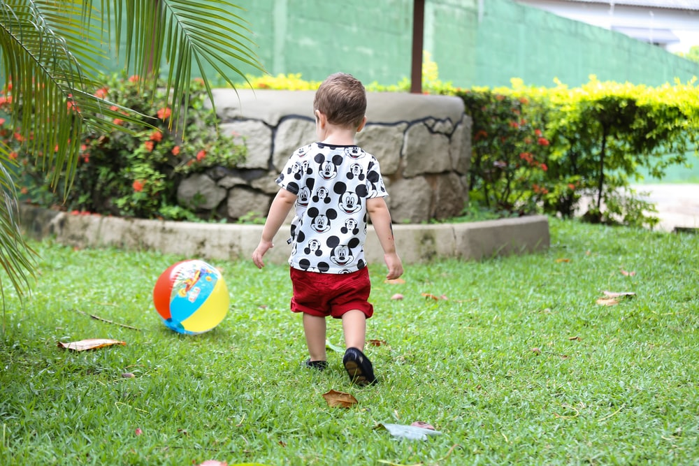 boy in white and black crew neck t-shirt and red shorts playing with ball on on on on on