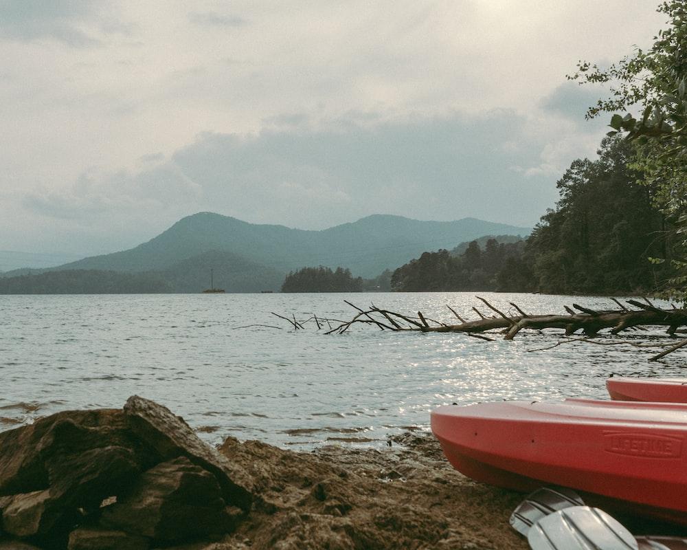 red kayak on brown rock near body of water during daytime