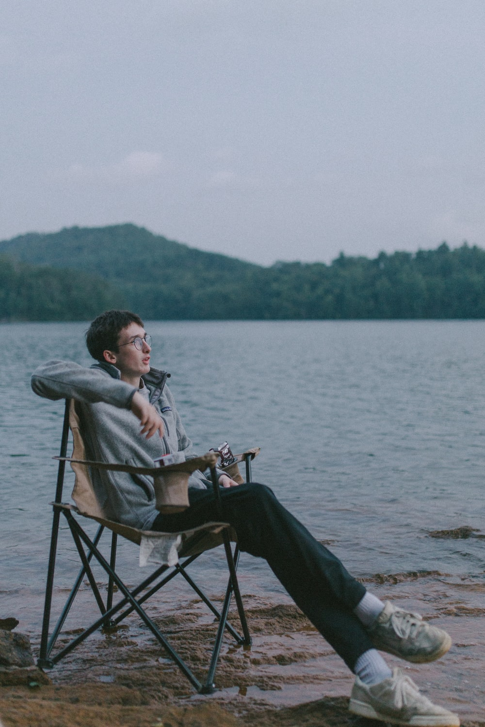 man in gray jacket sitting on black chair near body of water during daytime