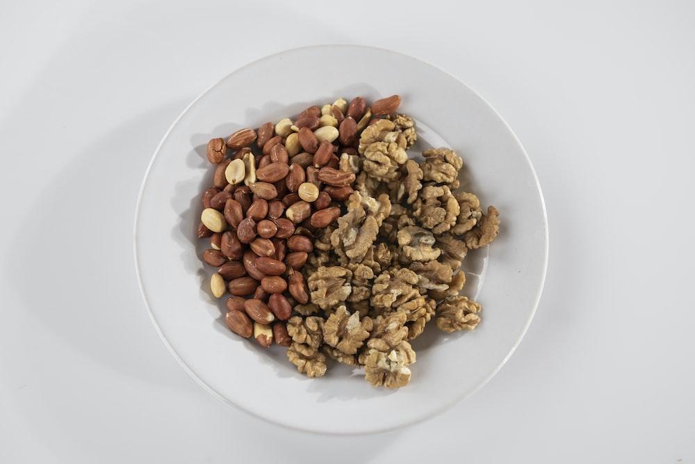 brown peanuts on white ceramic bowl