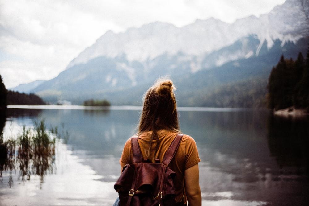 woman in pink shirt standing near lake during daytime