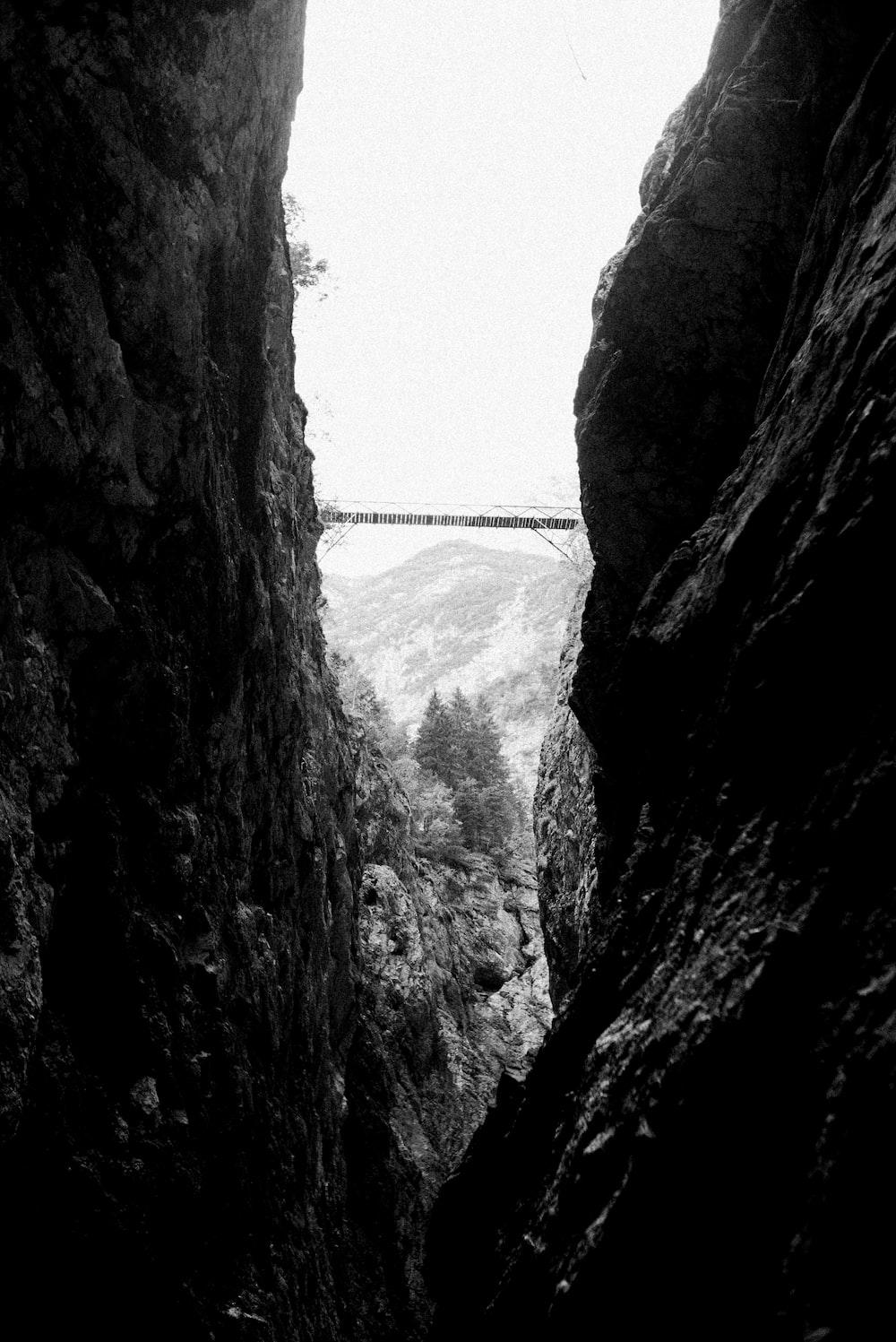 grayscale photo of bridge between rock formation