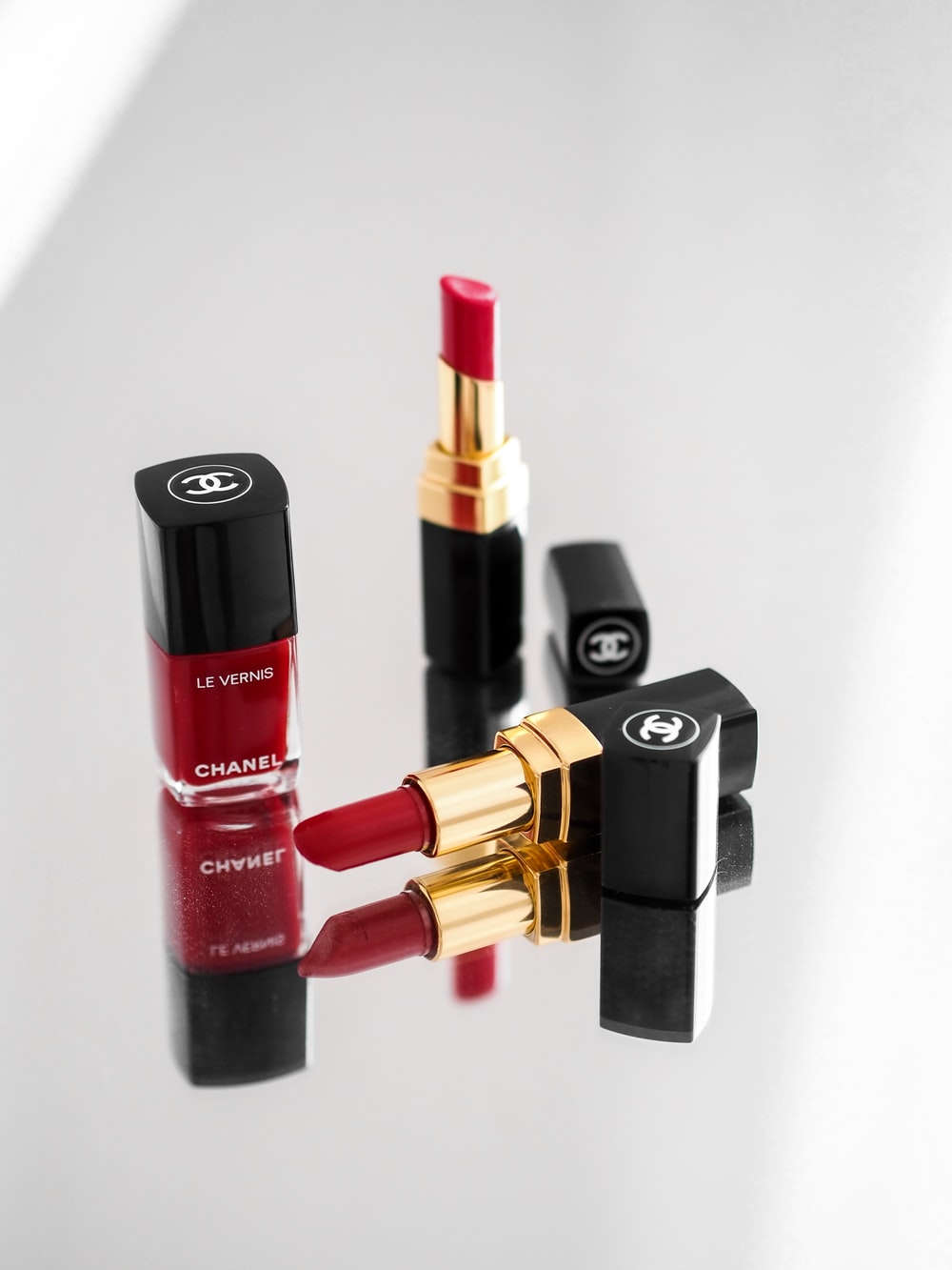 red and black lipstick beside red lipstick