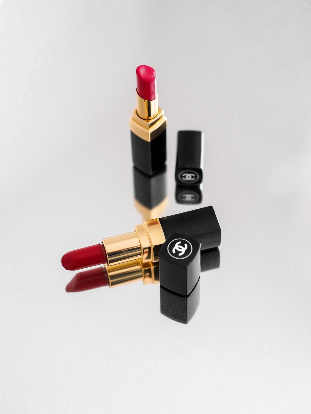 red lipstick beside black and gold lipstick