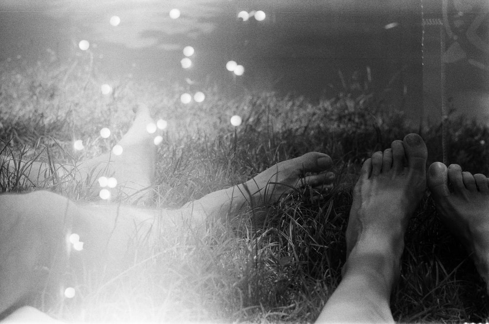 grayscale photo of persons feet on grass field