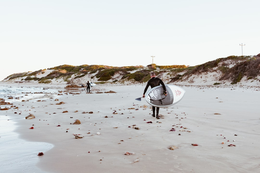 Person Carrying White Surfboard Walking On Beach During Daytime - unsplash