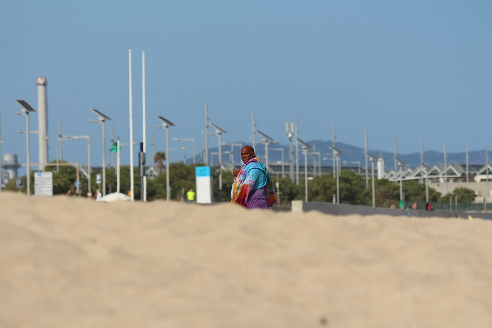 woman in red and blue dress sitting on brown sand during daytime
