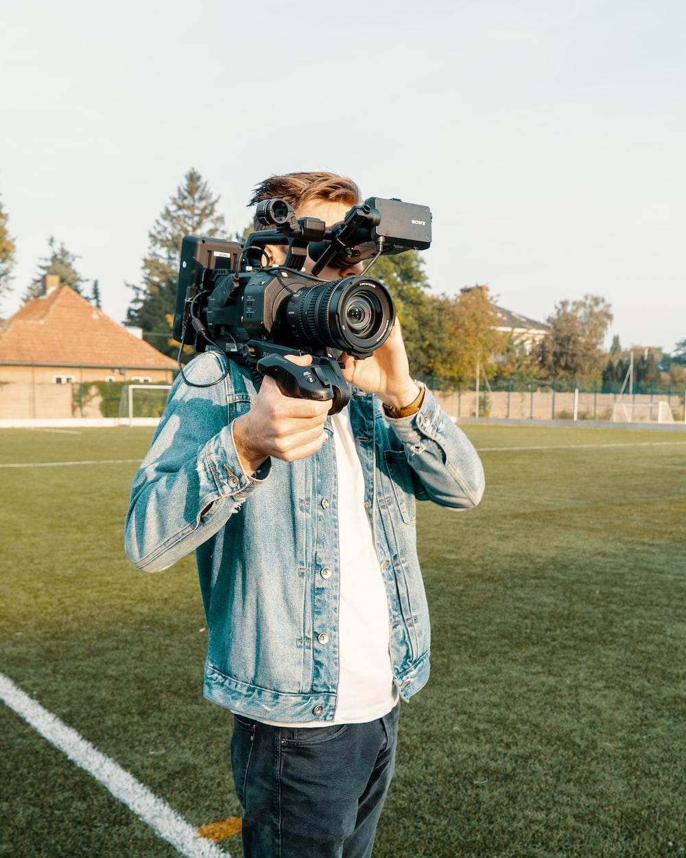 man in white and blue plaid dress shirt holding black dslr camera