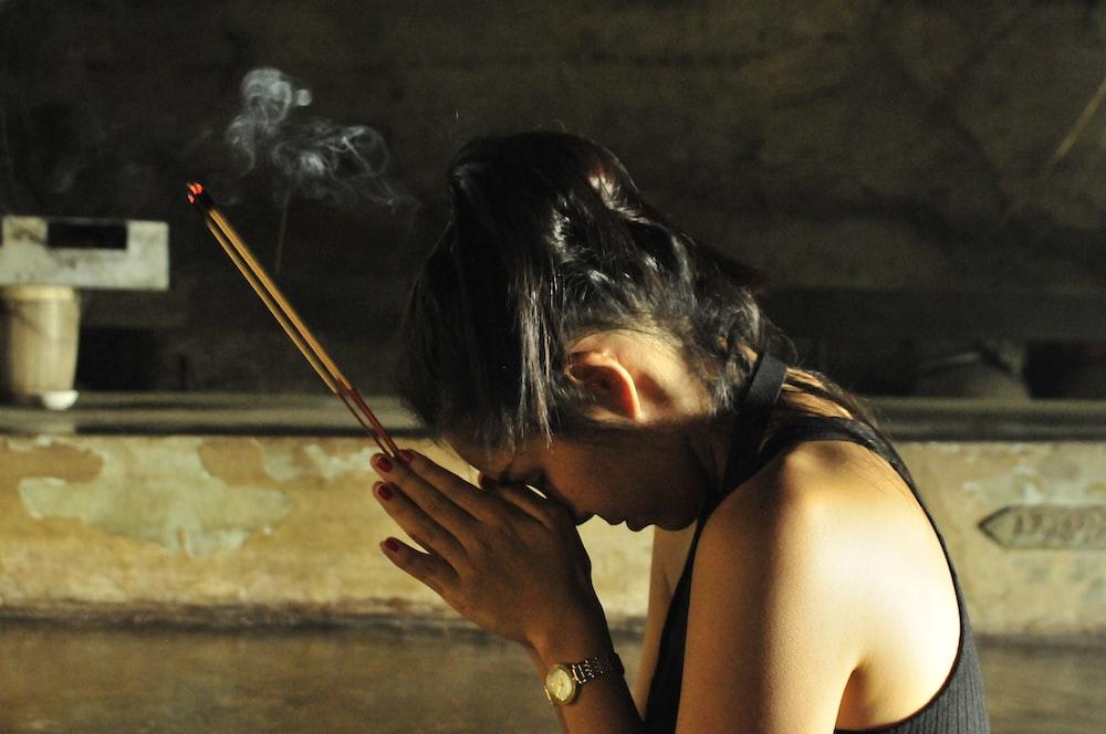 woman in black tank top holding cigarette stick