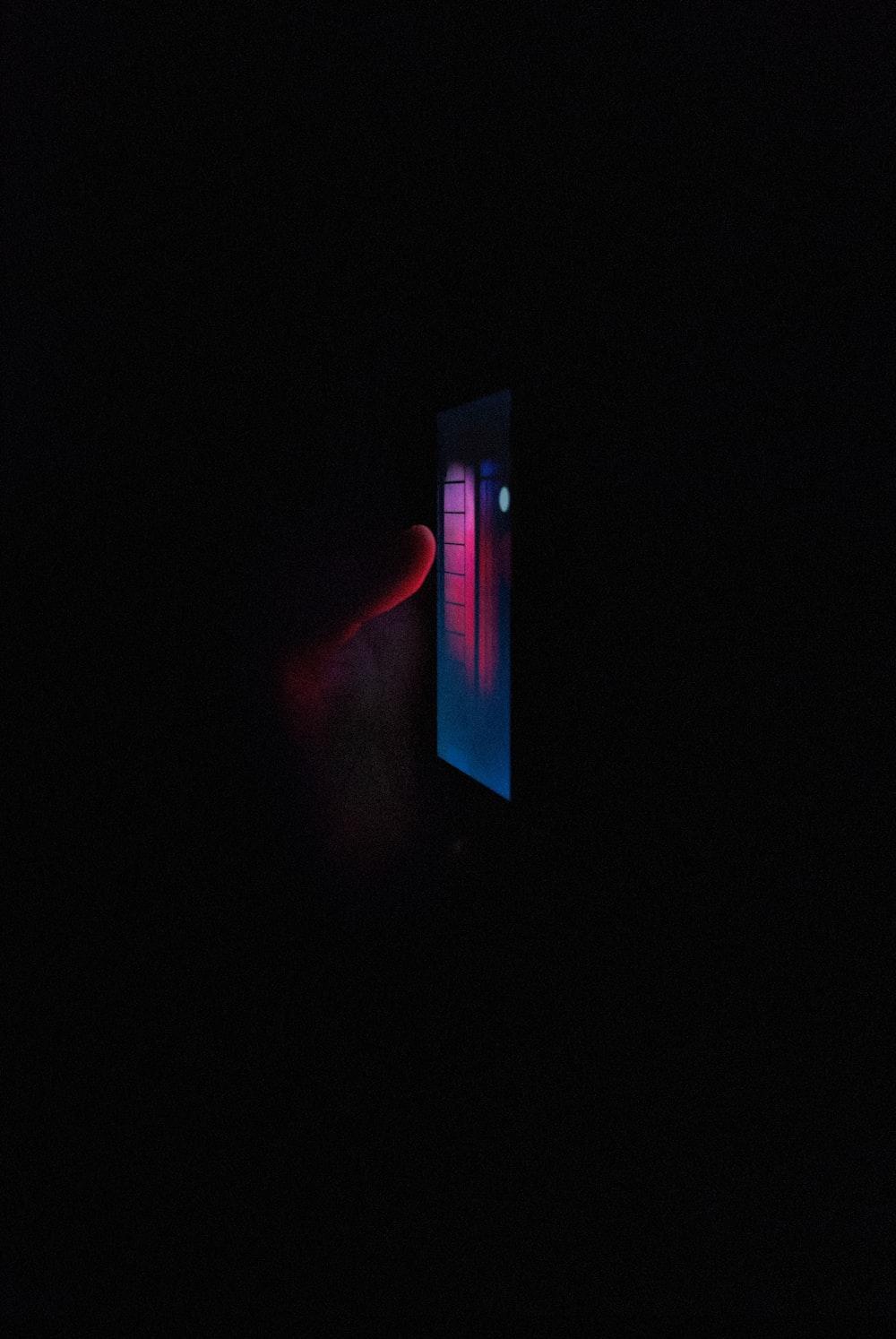 black flat screen tv turned on in dark room