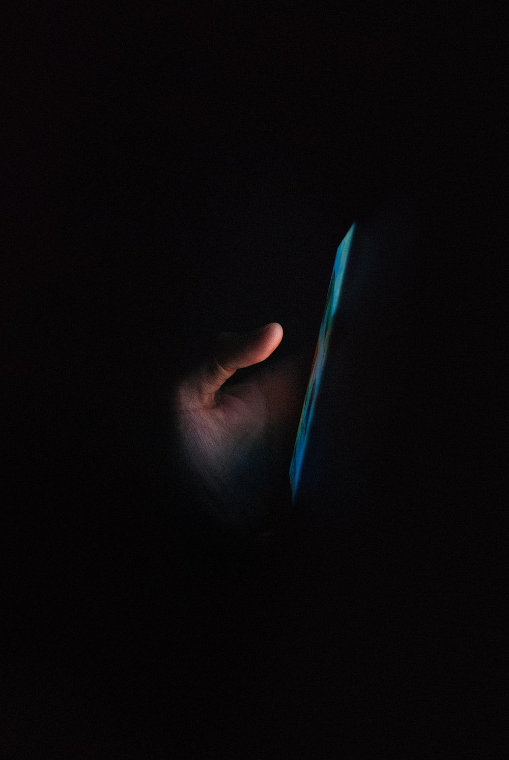 person holding blue light in dark room