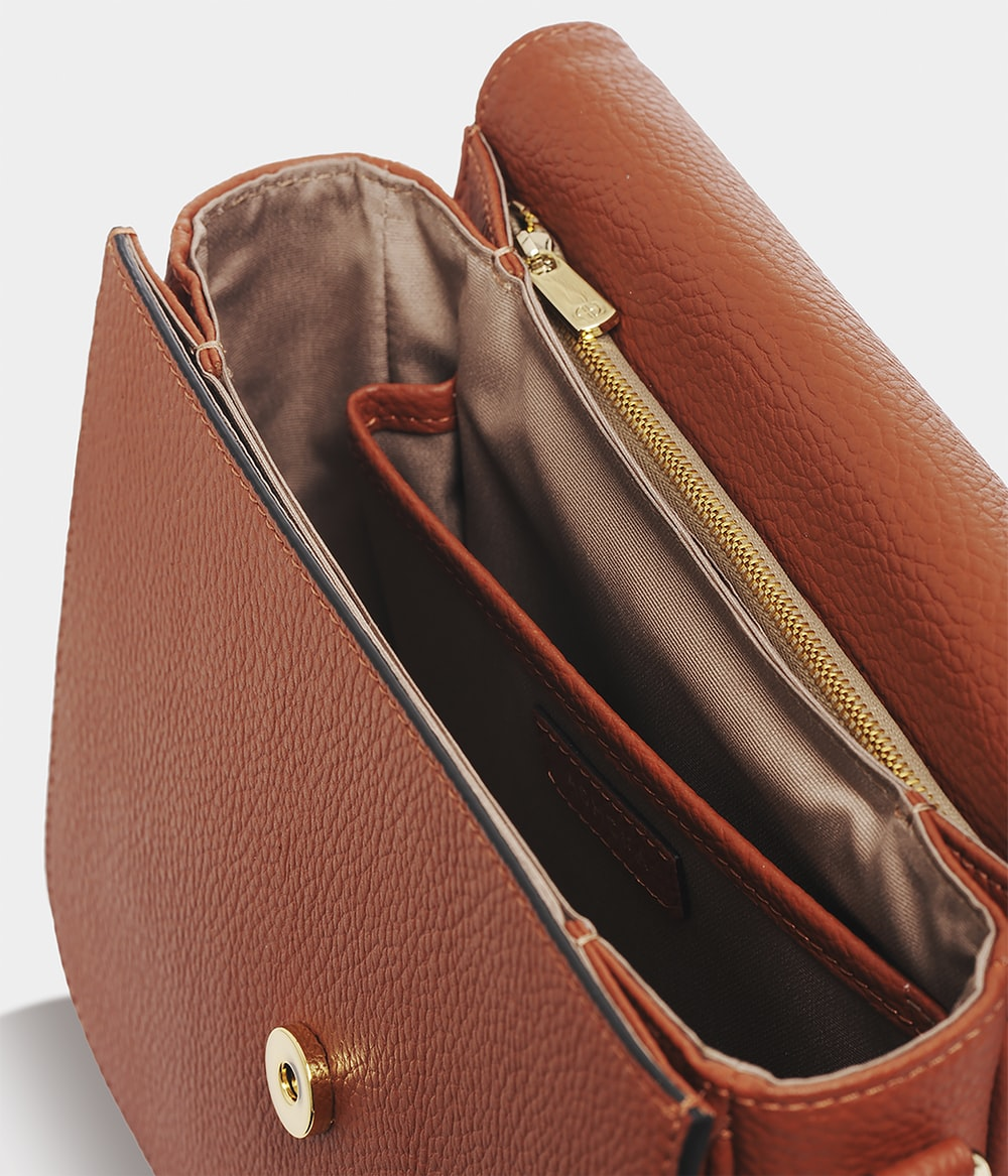 brown leather sling bag on white table
