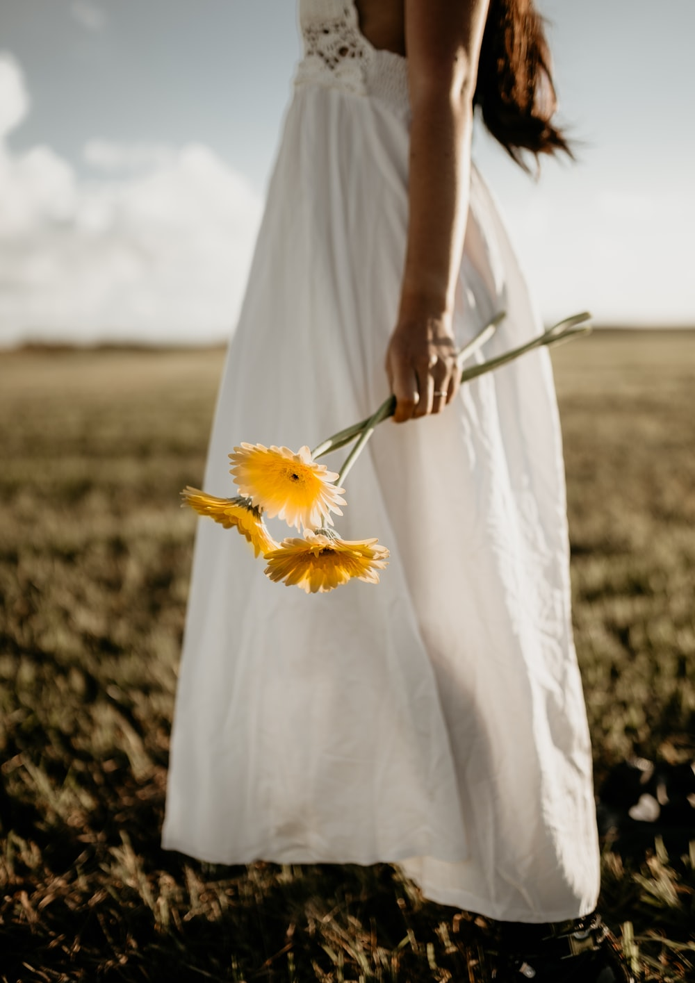 woman in white dress holding yellow flower