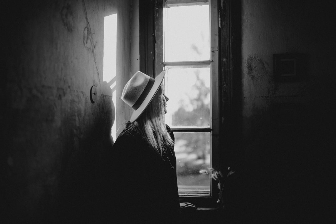 Woman In Black Shirt and White Fedora Hat Standing By the Window - unsplash