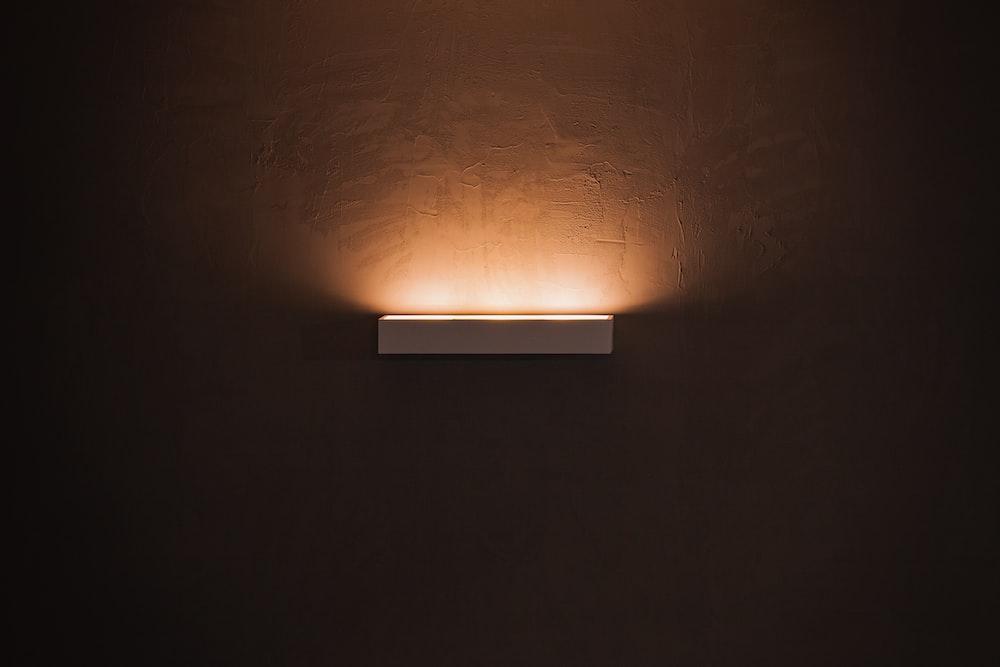 white light bulb turned on in dim lit room