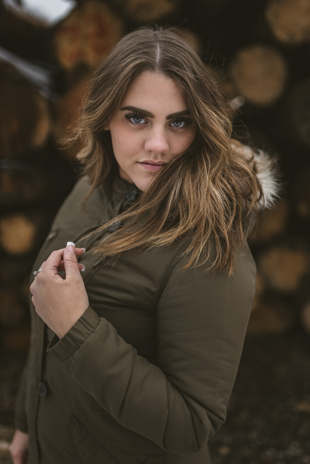 woman in black coat holding her hair
