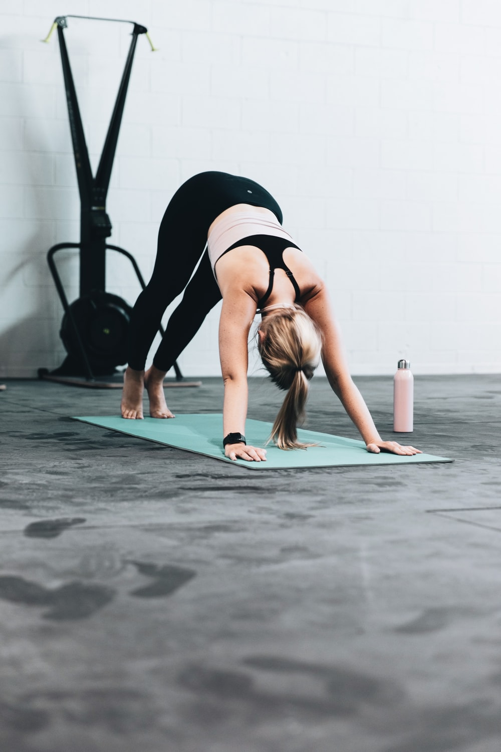 woman in black sports bra and blue denim jeans doing yoga