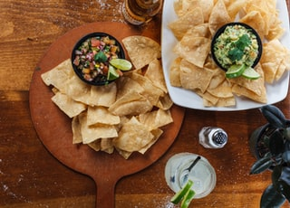 Overhead shot of chips salsa, guac, a margarita, and someone who is very irresponsible with the salt. Part of the C9 Work WordPress Theme sample content imagery.