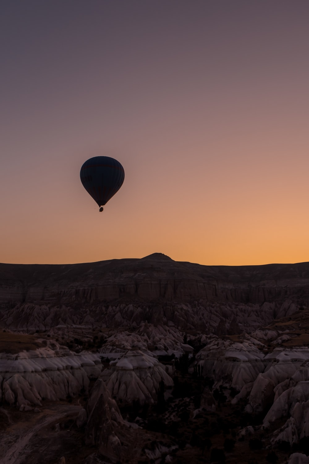 hot air balloon flying over the city during sunset