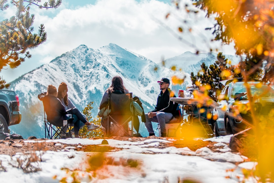 Friends Sitting Around Campsite With Epic Mountain View In Colorado Fall  - unsplash
