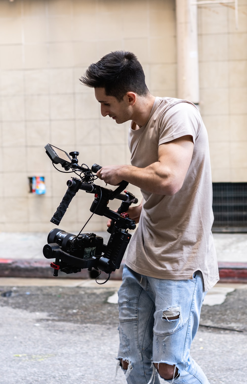 man in white t-shirt and blue denim jeans holding black video camera