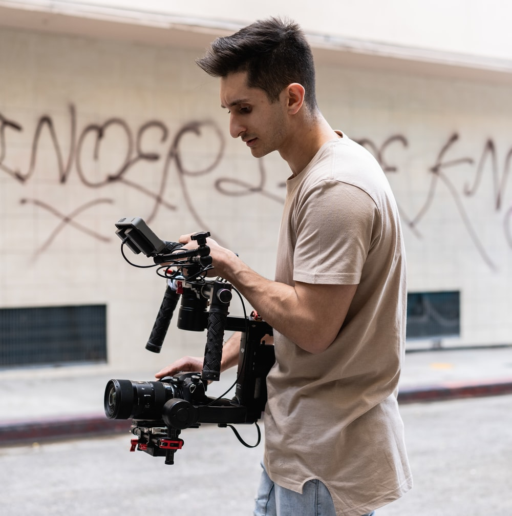 man in white t-shirt and gray pants holding black video camera