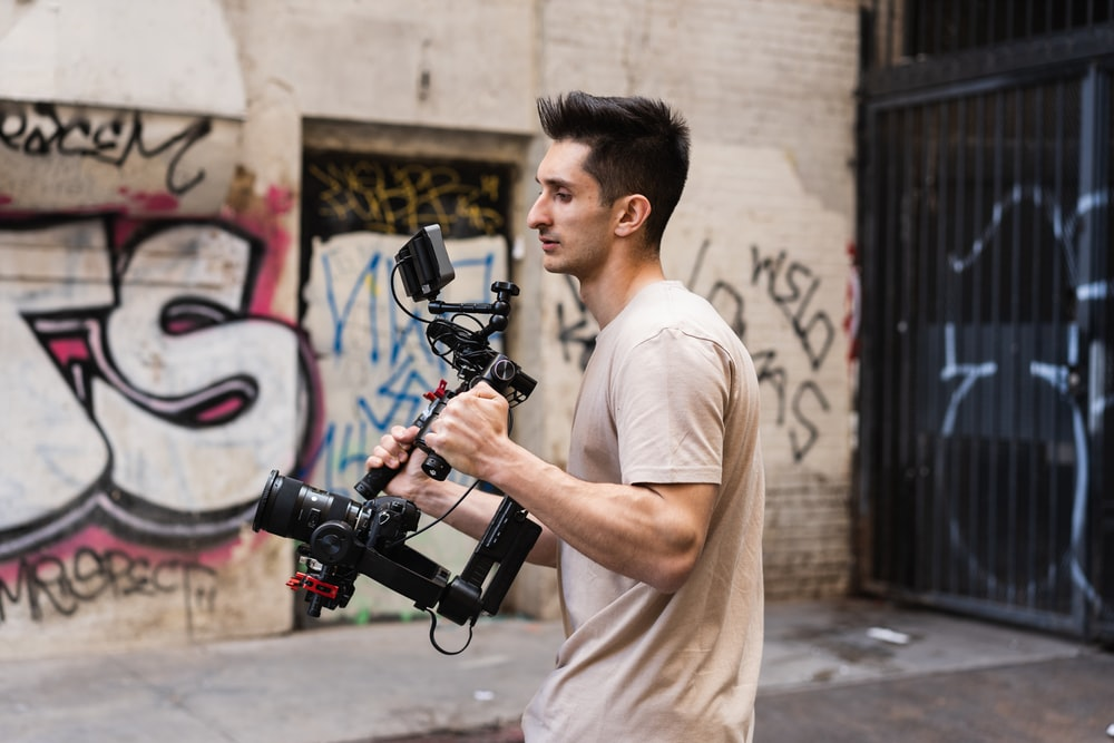 man in white t-shirt holding black dslr camera
