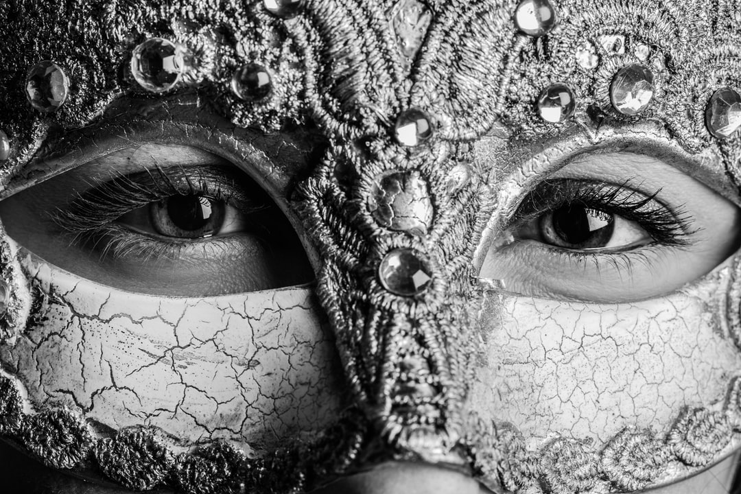 A Womanpeers Out To the Camera From Behind A Mardi Gras Mask. - unsplash