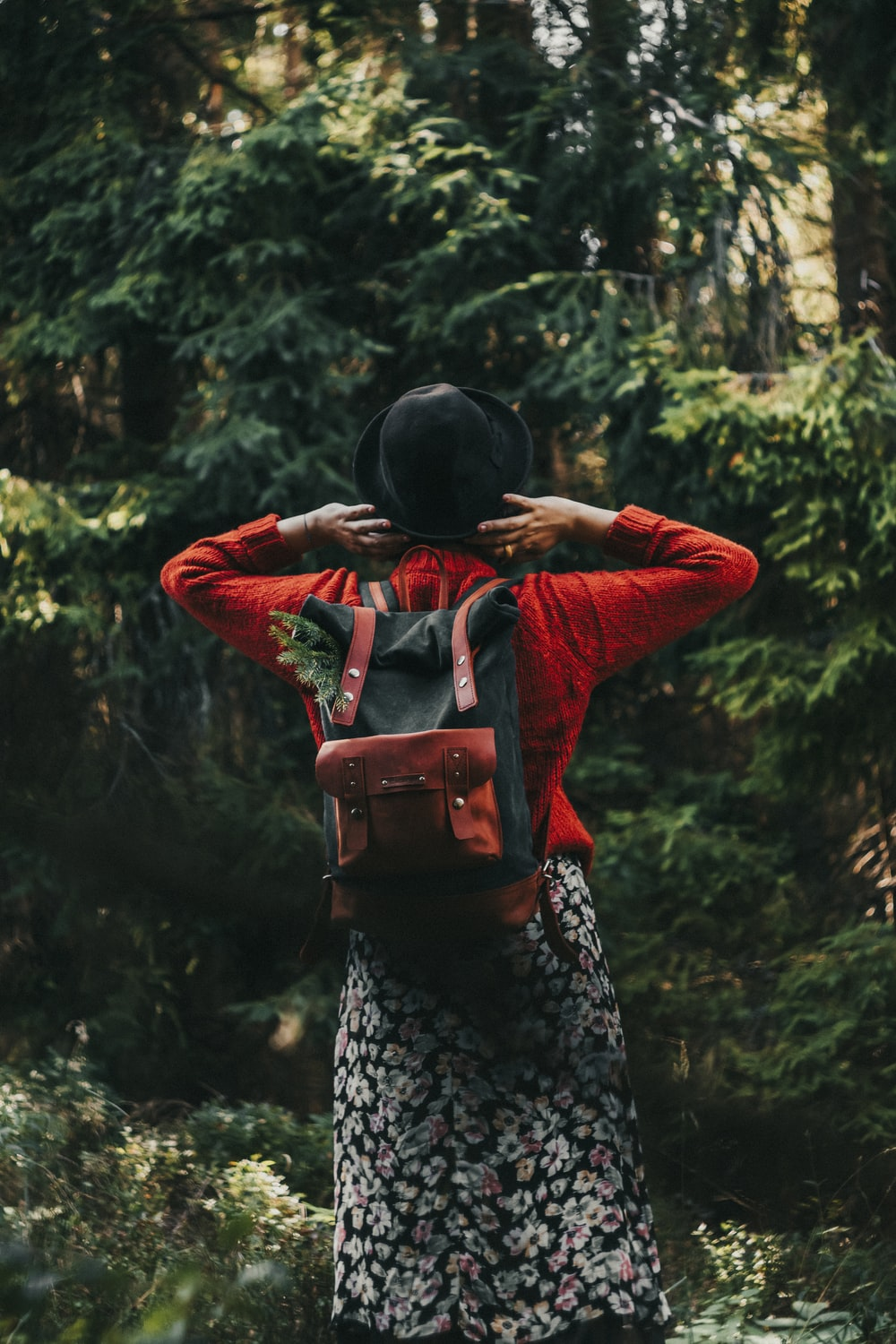 woman in red long sleeve shirt and black and white floral skirt carrying red backpack