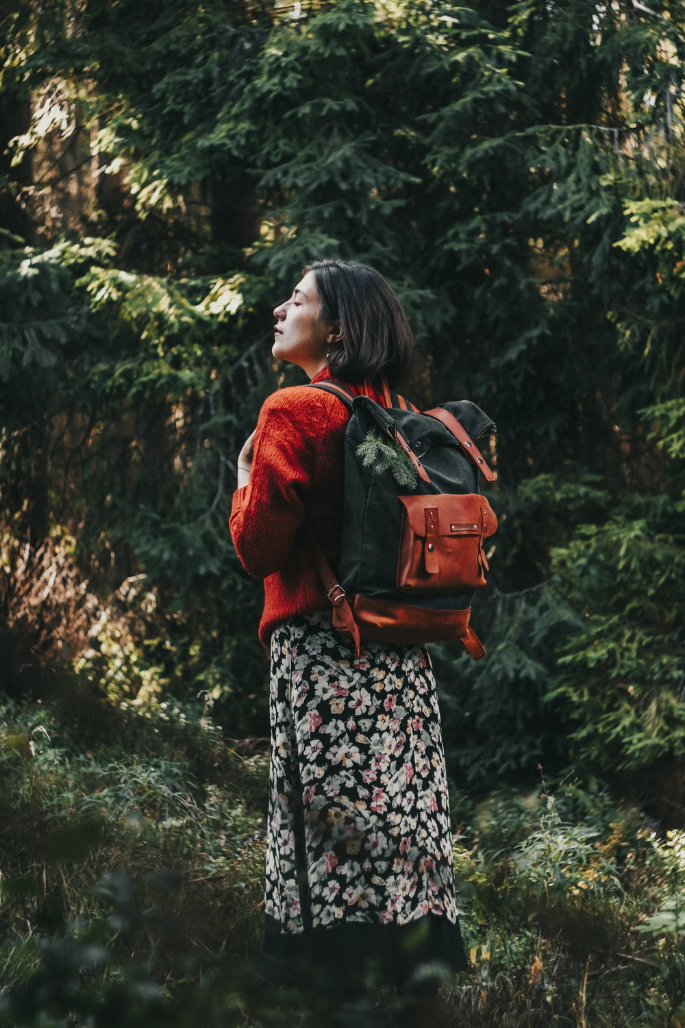 woman in red jacket carrying brown leather backpack