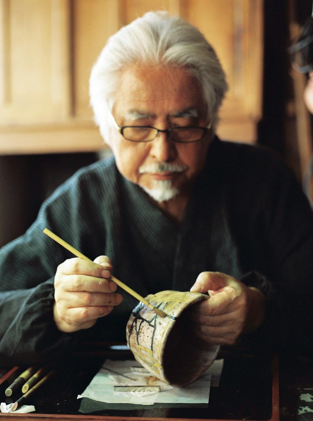 man in black sweater holding brown chopsticks