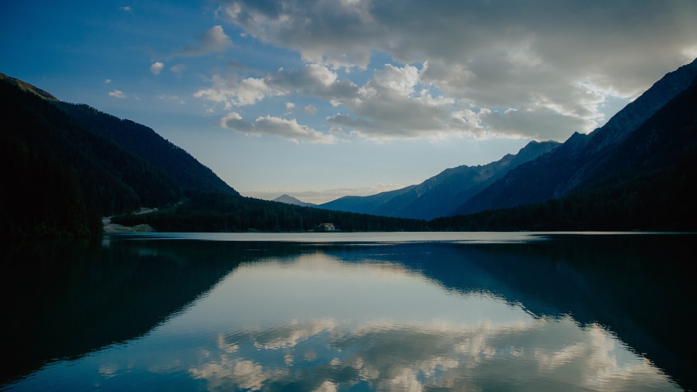 lake near mountain under white clouds and blue sky during daytime