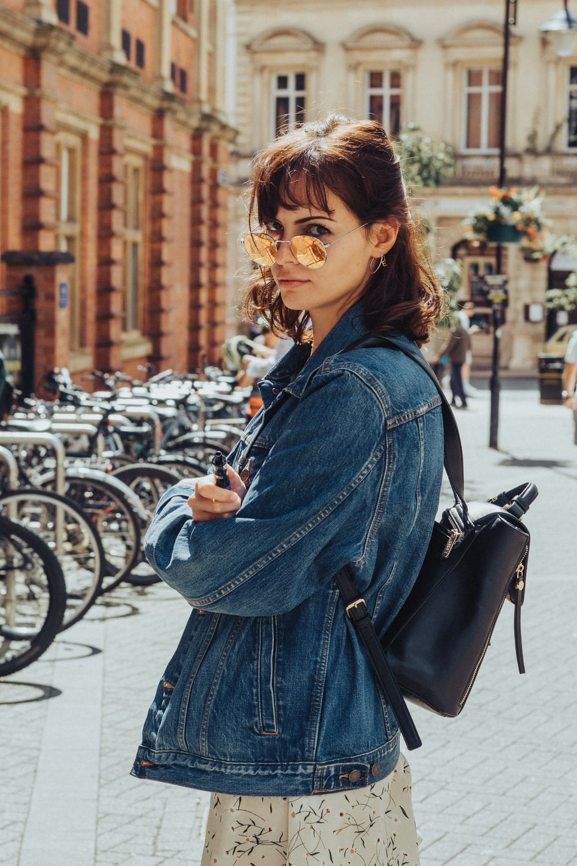 woman in blue denim jacket and blue denim jacket standing on sidewalk during daytime
