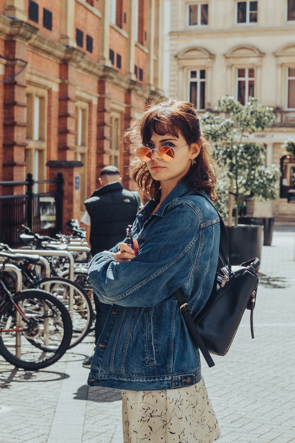 woman in blue denim jacket standing beside bicycle during daytime