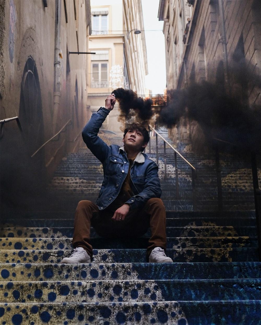 man in blue denim jacket sitting on concrete bench