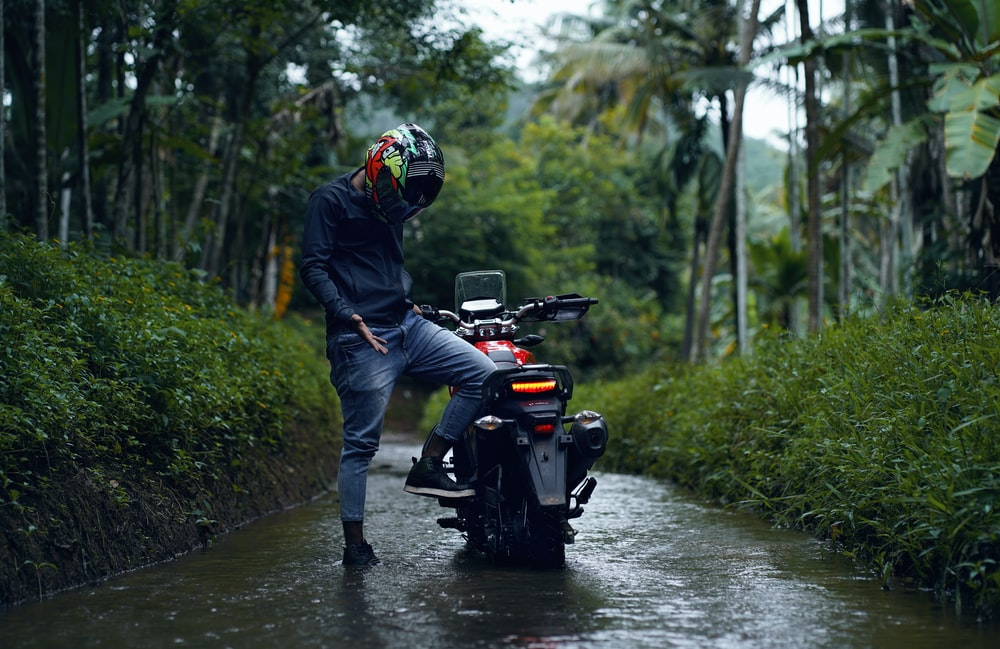 man in black jacket riding on black and red atv