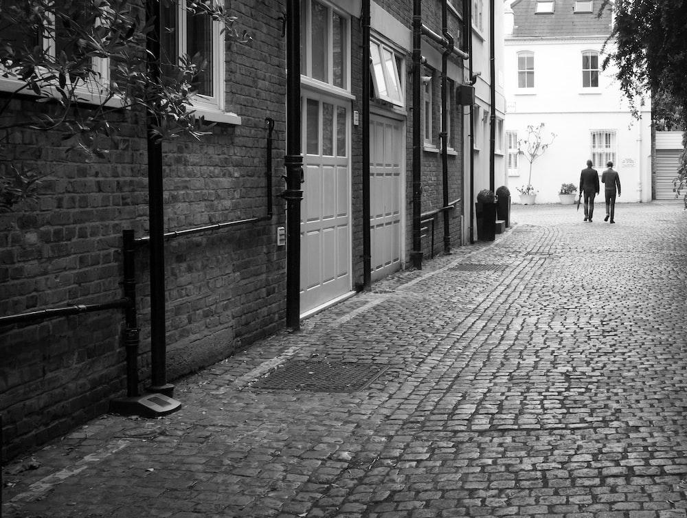 grayscale photo of brick pavement