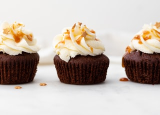 three cupcakes on white surface