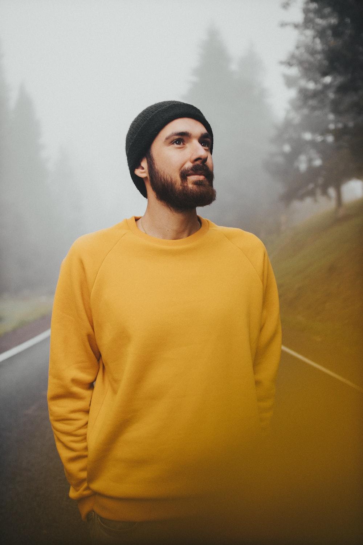 man in yellow turtleneck sweater standing near green grass field