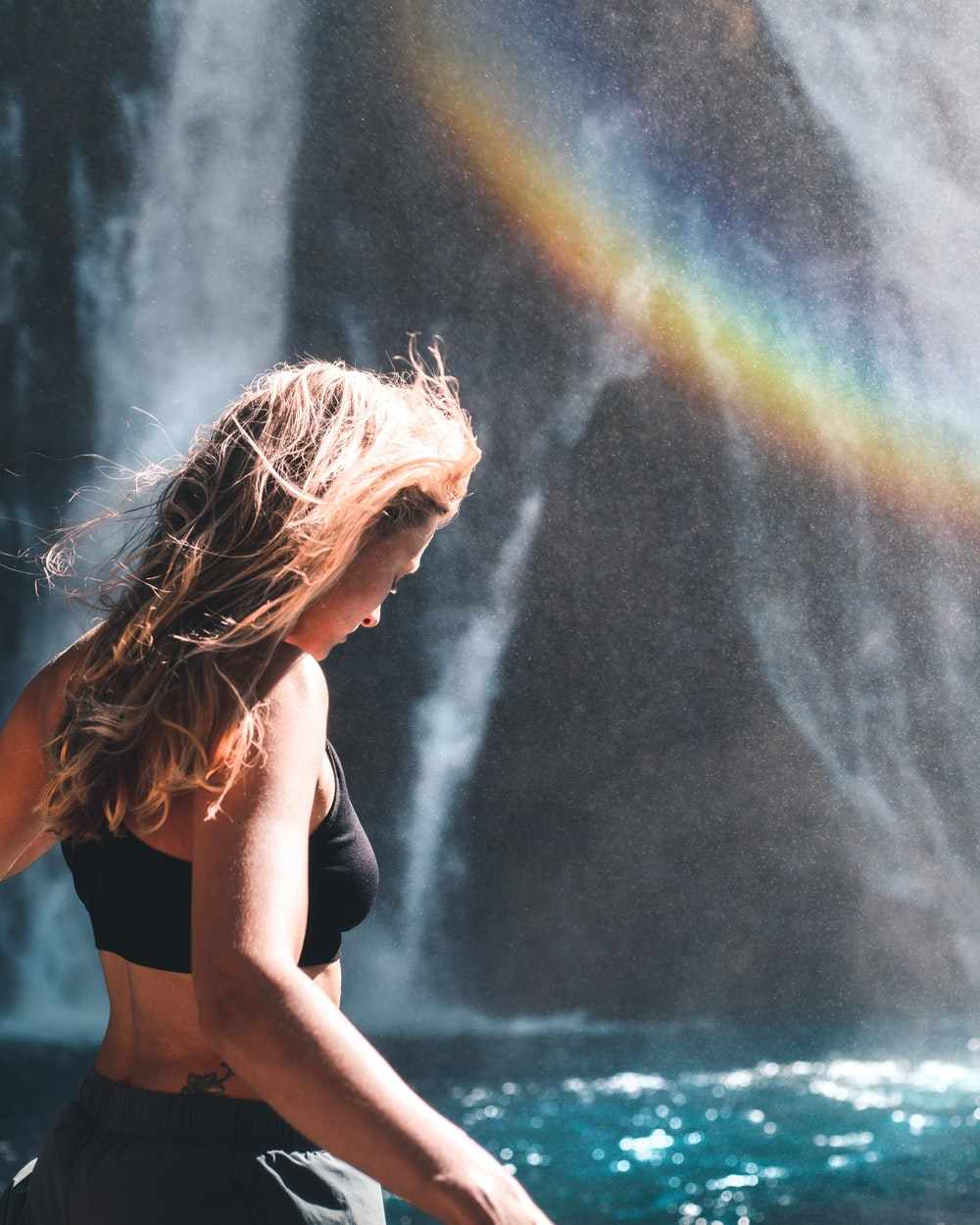 woman in black sports bra and blue denim shorts standing in front of waterfalls