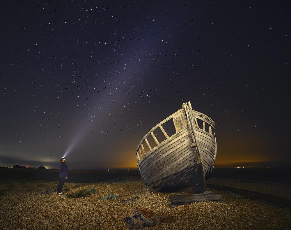 man standing beside brown wooden boat under starry night