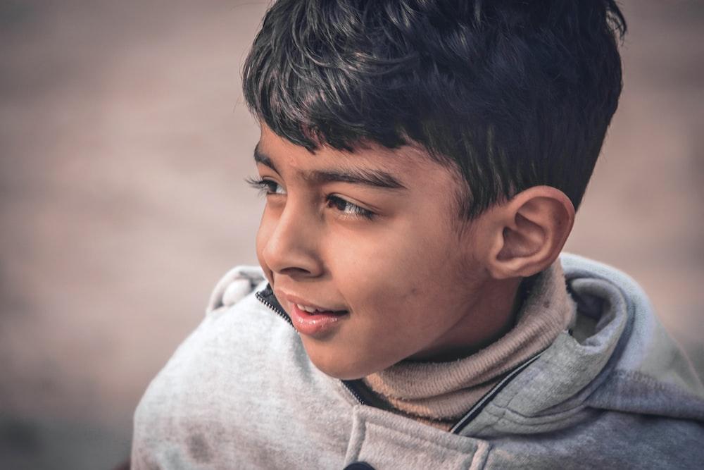 boy in gray hoodie smiling