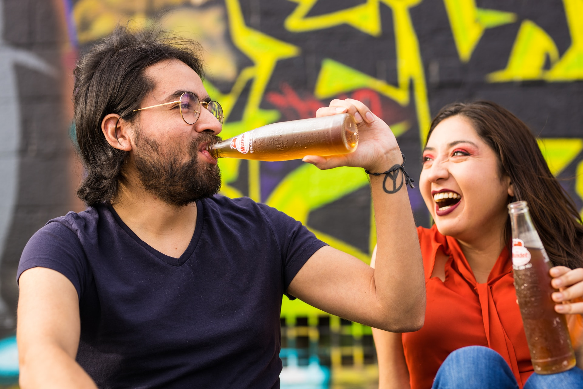 man in black crew neck t-shirt holding woman in red sleeveless dress drinking beer